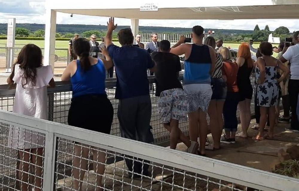 O presidente Jair Bolsonaro (ao fundo) cumprimenta apoiadores ao deixar o Palácio da Alvorada após ter anunciado que teste de coranavírus deu negativo — Foto: Guilherme Mazui / G1