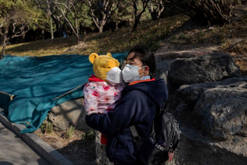 Mulher com máscara de proteção contra o coronavírus segura urso também com máscara em parque em Pequim, na China, neste sábado (14) — Foto: Nicolas Asfouri / AFP